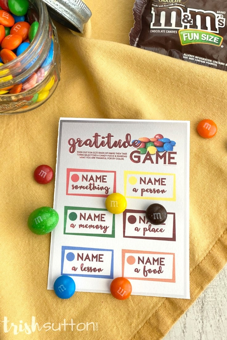 Gratitude game card with color coded M&M candies on a yellow fabric backdrop.