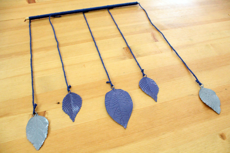 5 metal leaves painted in shades of blue hanging from a wooden dowel