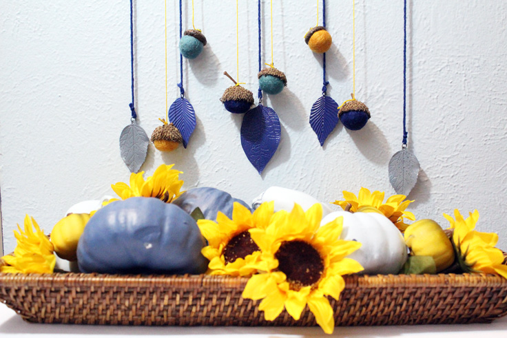 acorn and leaf fall wall decor hanging over a basket of matching painted pumpkins and sunflowers
