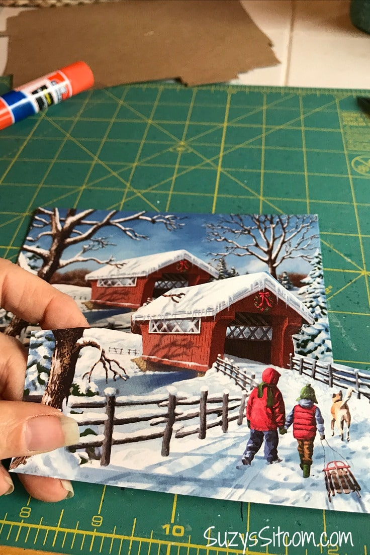 Cutting holiday cards to make layered paper art.