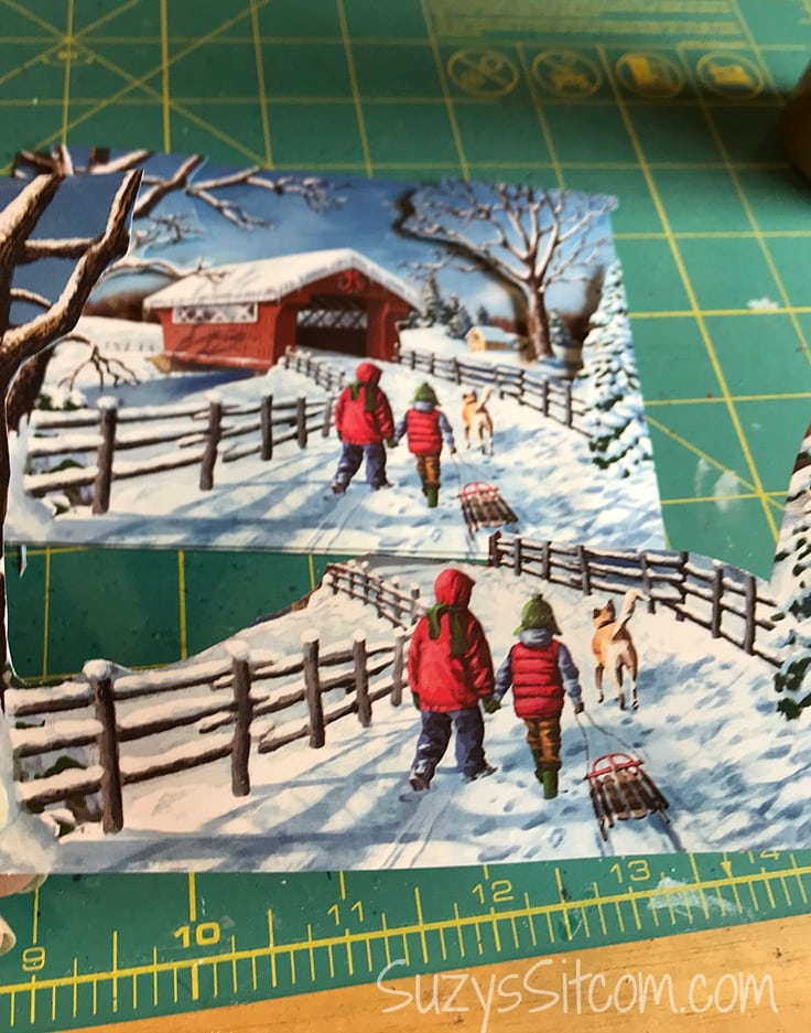 Gluing different parts of the winter scene together to make layered paper art.