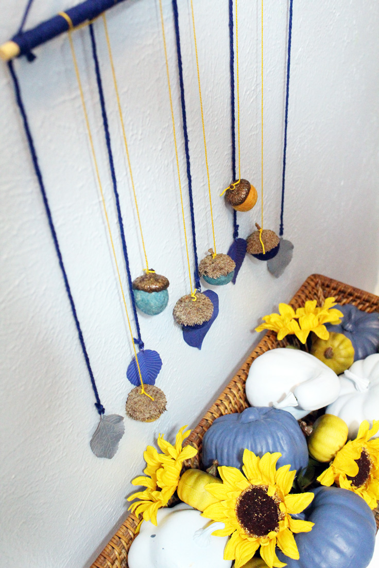 acorn and leaf wall decor hanging displayed over a blue pumpkin and sunflower centerpiece
