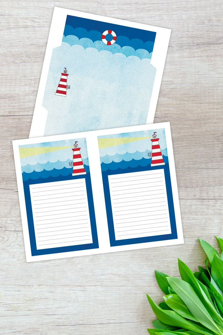 Envelope template and lined stationery paper with lighthouse design on desk with foilage.