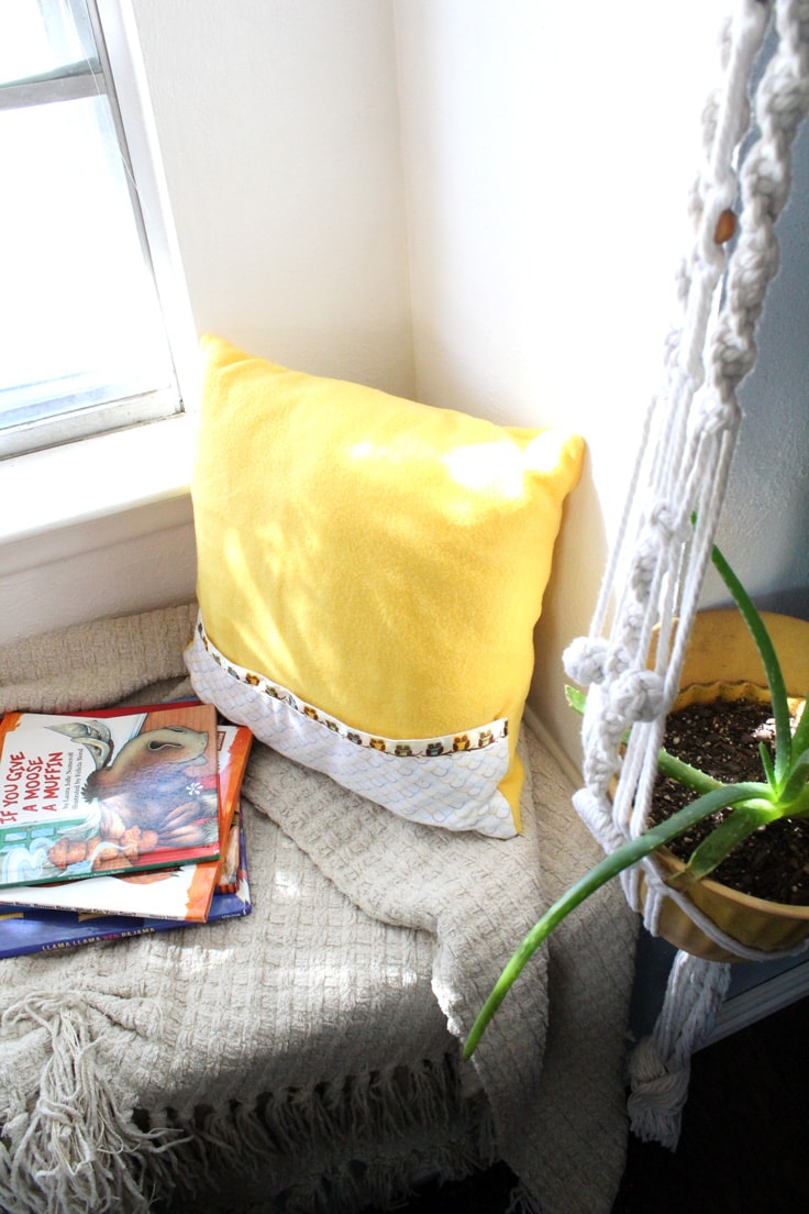 a yellow pillow with a pocket sitting in a window seat beside a stack of children's books