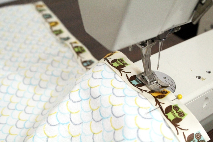 closeup of a sewing machine stitching a ribbon to the edge of fabric