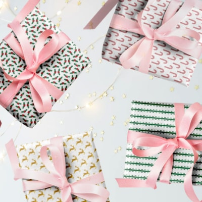 View of 4 wrapped gifts on white background with twinkling lights and gold stars.