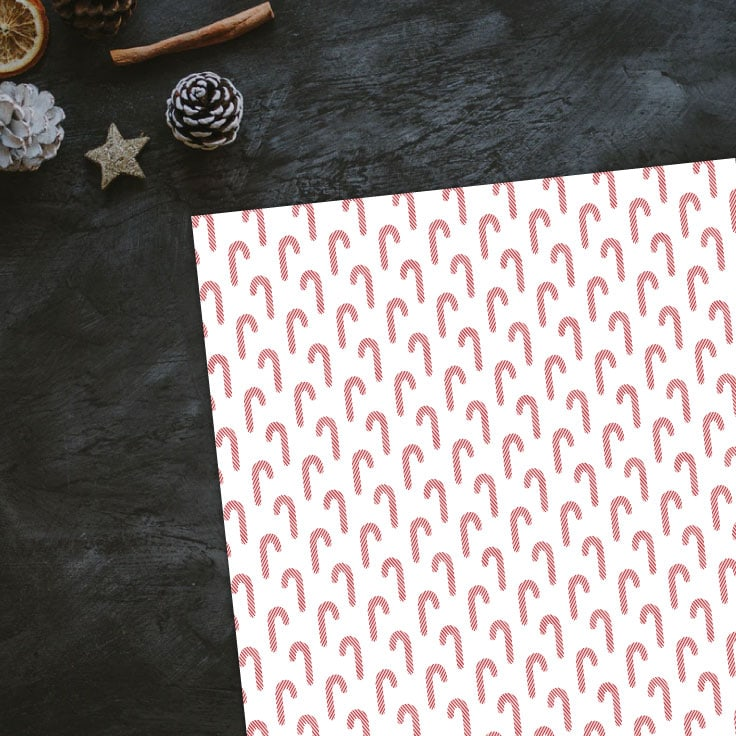 Preview of candy canes wrapping paper on dark black countertop with pinecone and stars decorations.