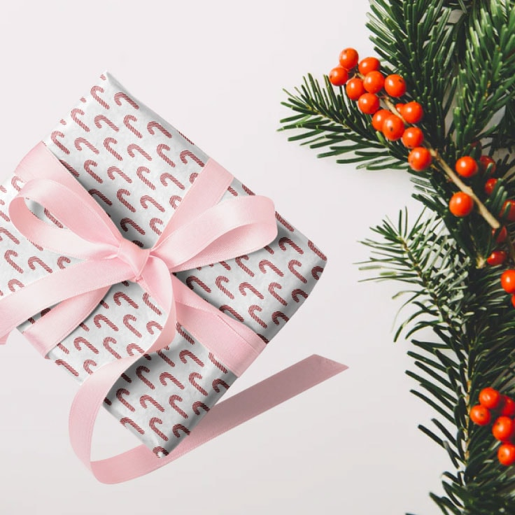 Small gift wrapped in candy canes paper design with pink ribbon with evergreen leaves and red berries on the side as decoration.