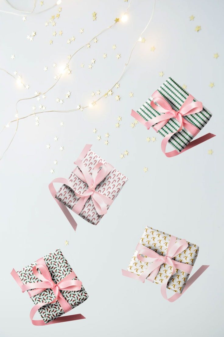 White desk with gold stars and lights decoration and four little gift boxes wrapped with pink ribbon.