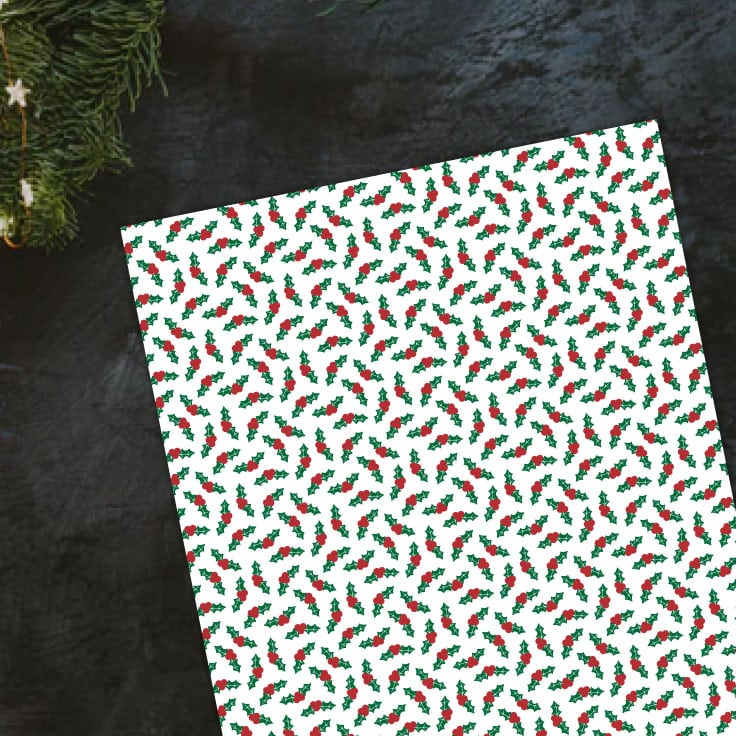 Preview of holly leaves paper design on black countertop with evergreen holiday decor in the top left corner.