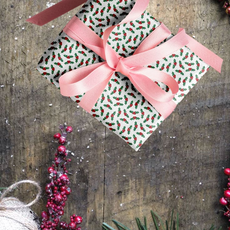 Gift with holly leaves wrapping paper and pink ribbon on top of rustic wooden surface and red berries decorations.