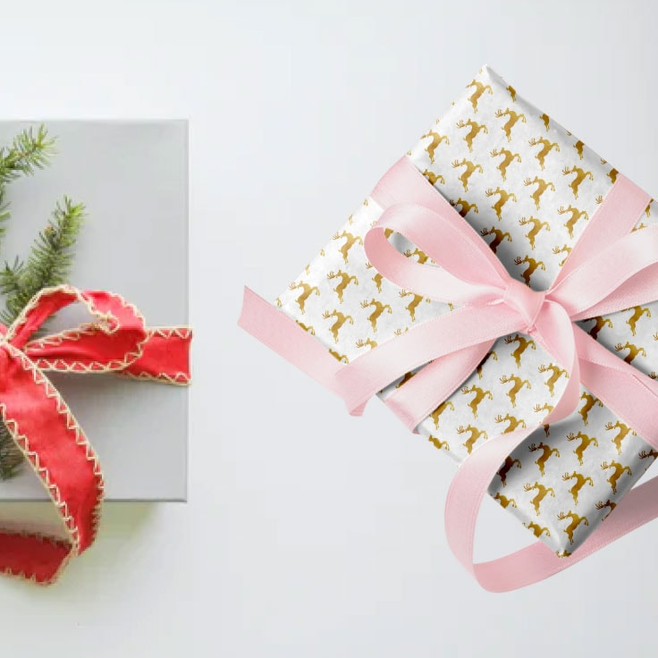 Two wrapped gifts on a white surface: one gray box with red ribbon and evergreen sprig and one box wrapped in gold reindeer print with a pink ribbon.