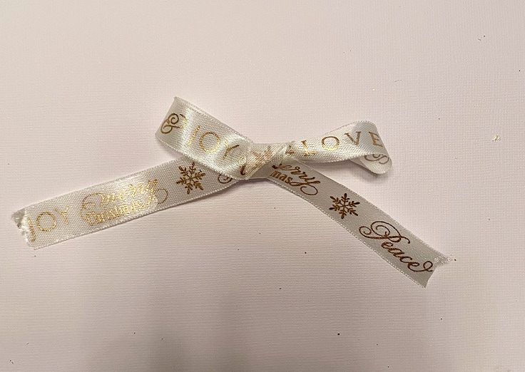 closeup view of a white Christmas ribbon tied in a bow