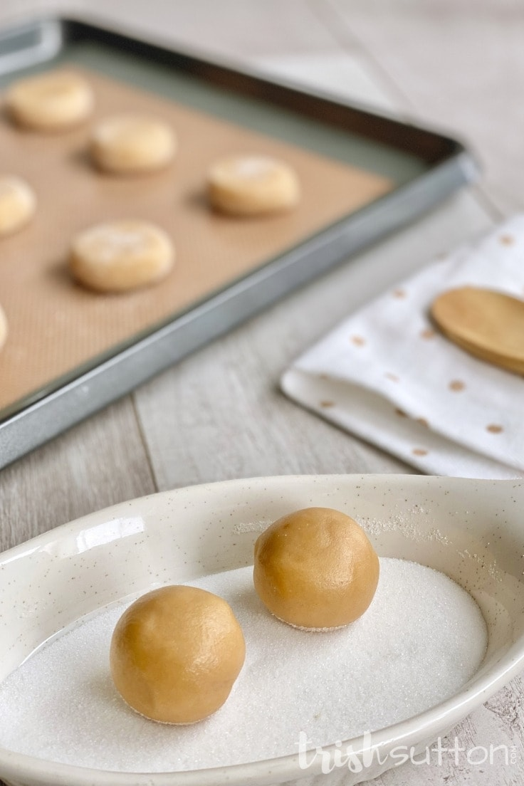 Two dough balls in a dish of sugar with a baking sheet ready to go in the oven.