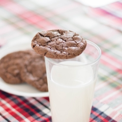 A chocolate cookie sitting on a tall glass of milk.