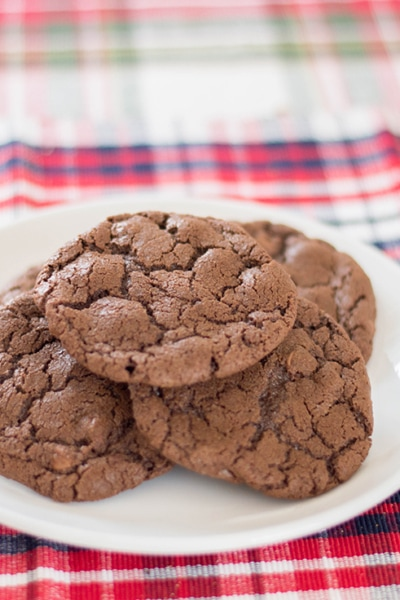 A plate full of chocolate cookies made out of a simple brownie mix on a plaid place mat.