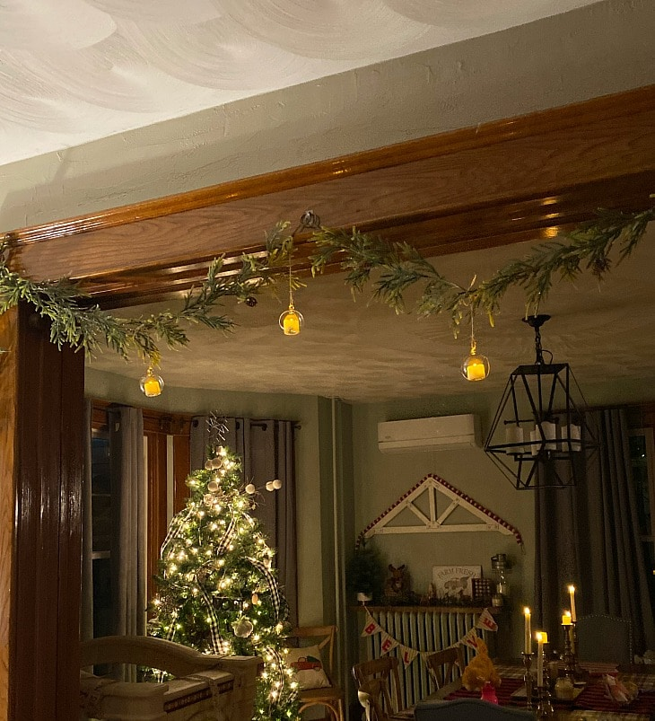 A living room decorated for Christmas with greenery, a decorated tree, and candles on the dining table