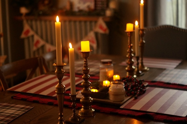A dining table decorated for Christmas with several types of candles