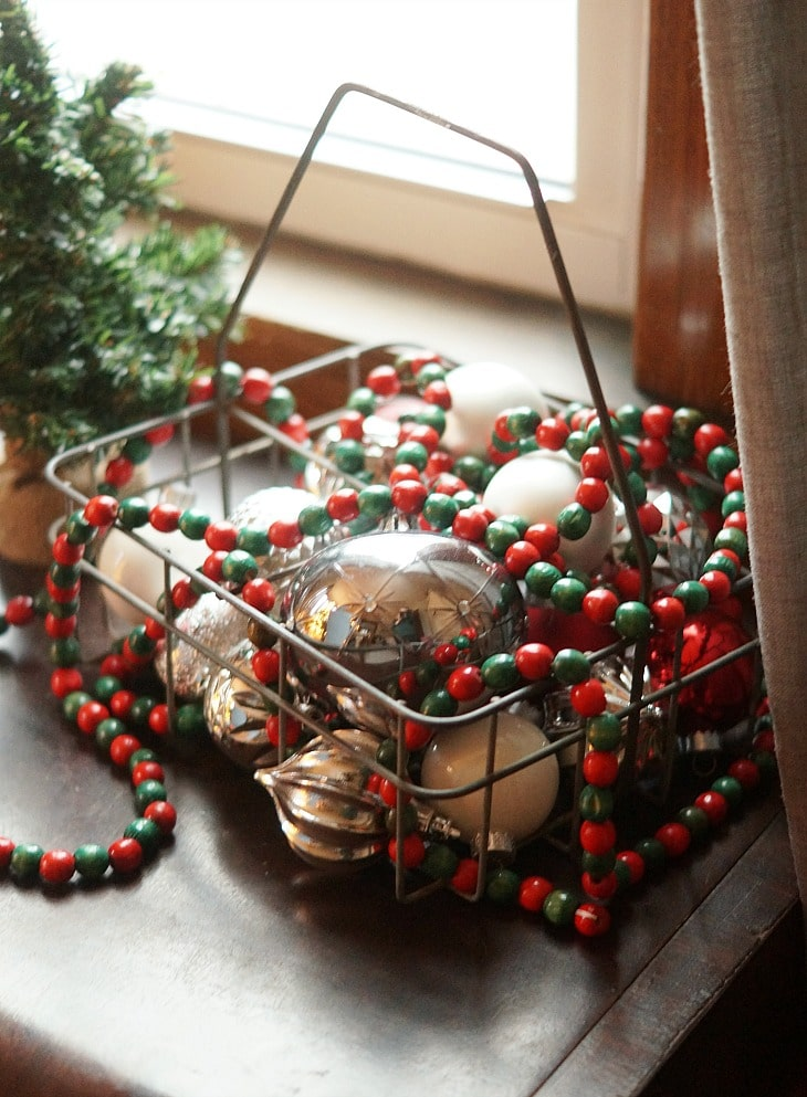 A basket with Christmas ornaments in it and some garland on top