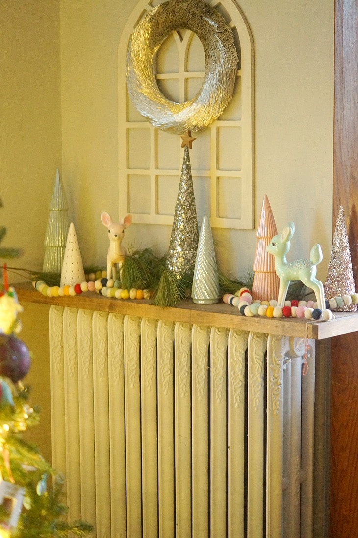 A mantel decorated for Christmas with garland, ceramic figures, and greenery