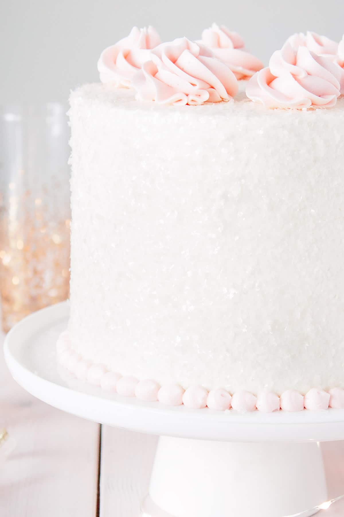 Pink champagne cake with white frosting coasted in sparkling sugar