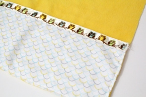 fabric pocket sewn to the bottom of a piece of yellow fleece fabric