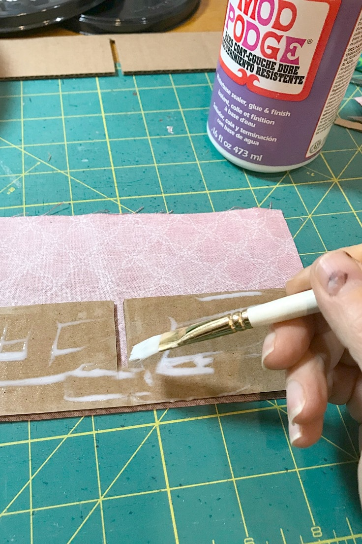 Painting mod podge on the cardboard with a small brush to attach fabric