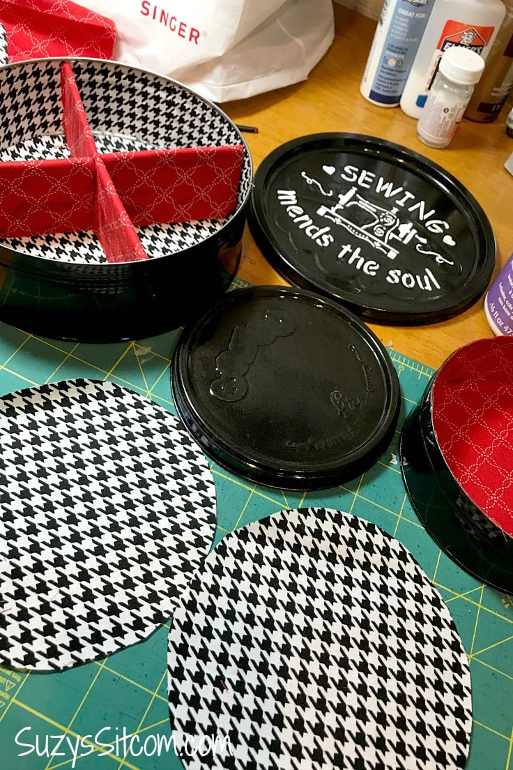 A cookie tin painted black with white accents and lined with houndstooth fabric and a red fabric divider