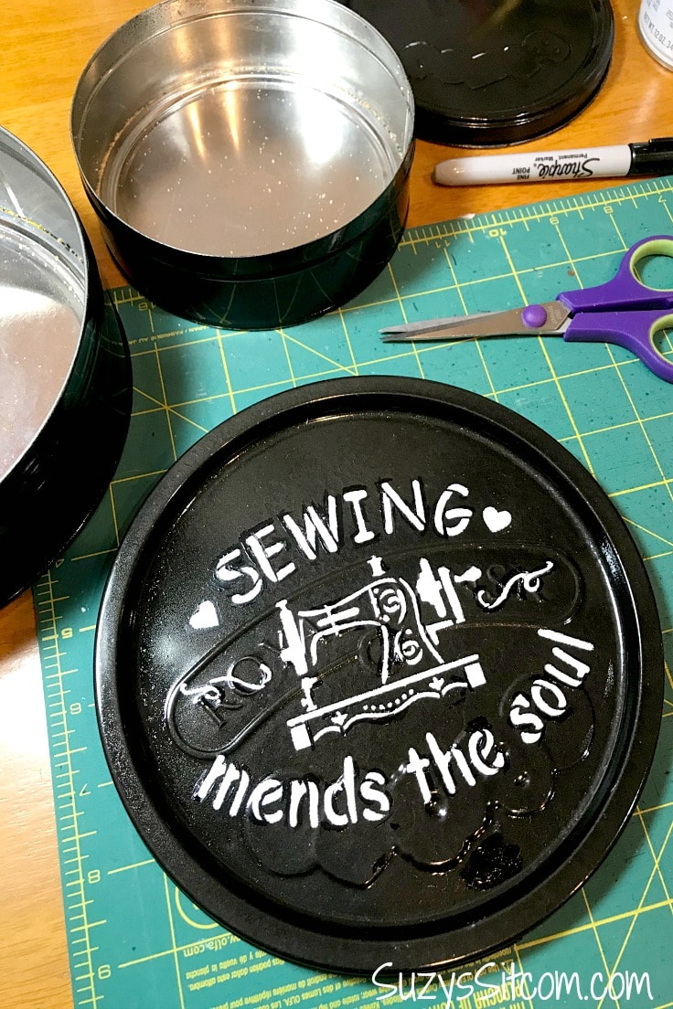 A black painted cookie tin with a new stenciled design on top of the lid in white that says