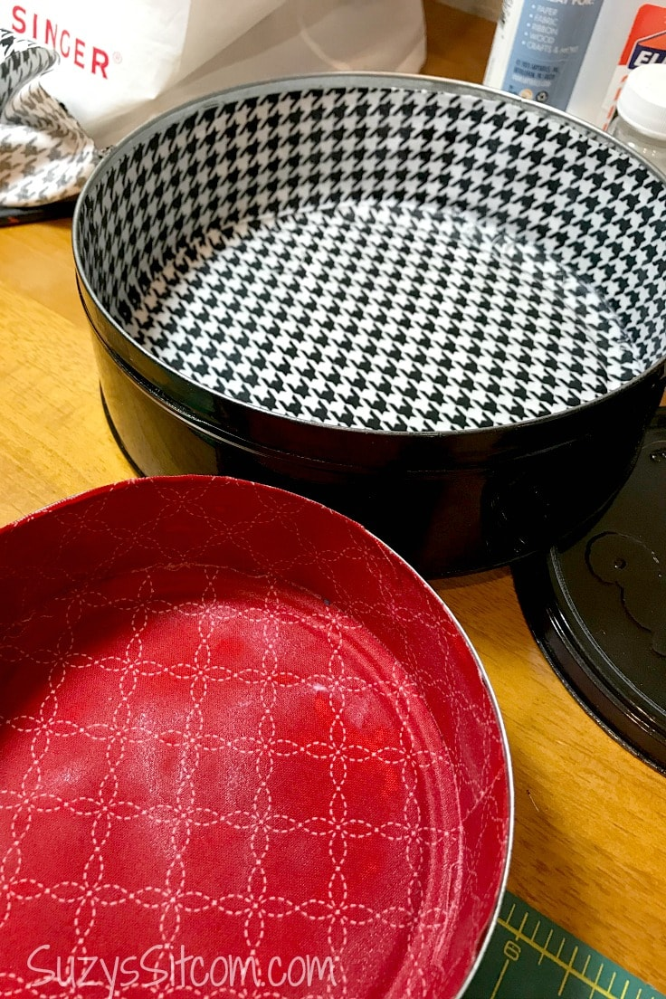 2 fabric-lined cookie tins, one with houndstooth and the other in a red patterned fabric