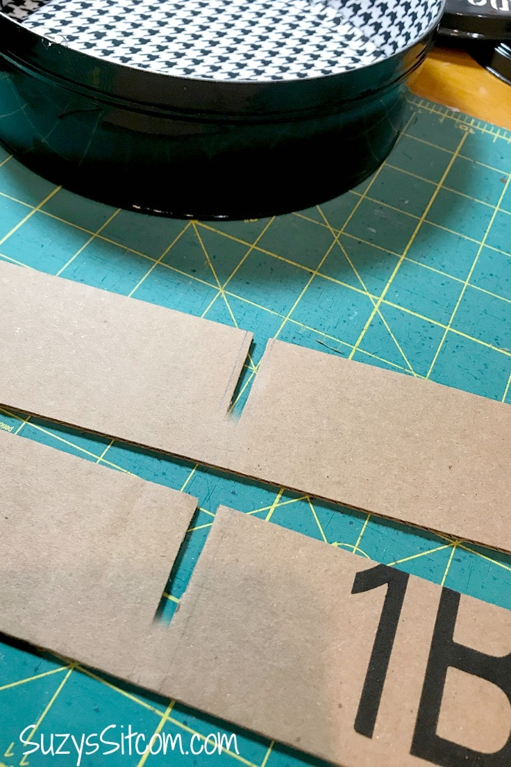 Cutting long strips of cardboard with notches as DIY dividers inside the tin