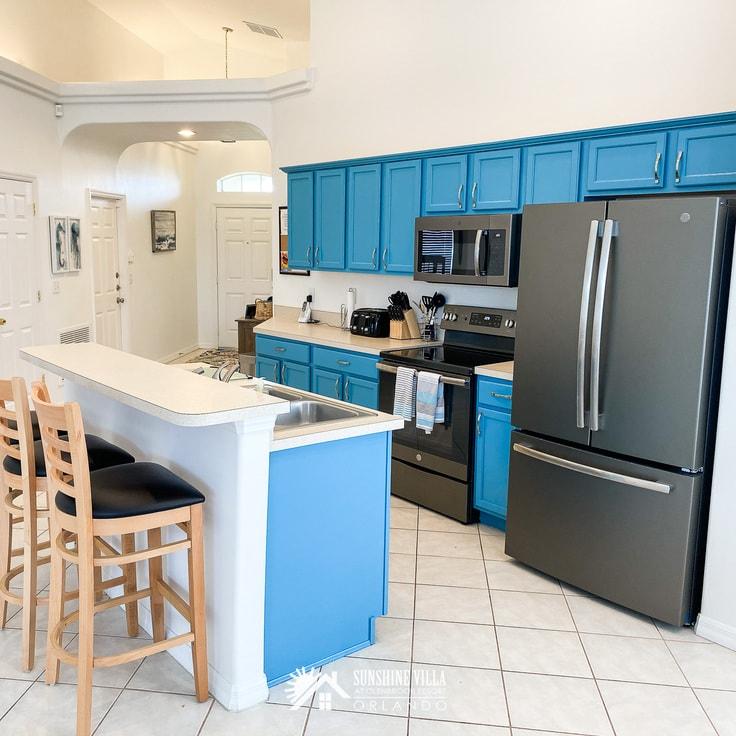 Sunshine Villa kitchen with black appliances and bright blue cabinets