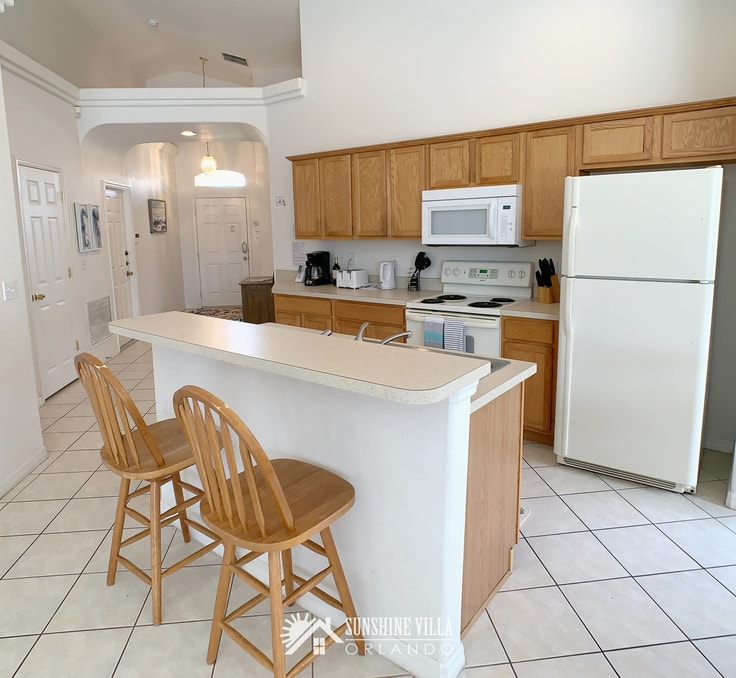 Sunshine Villa kitchen with white appliances and brown cabinets