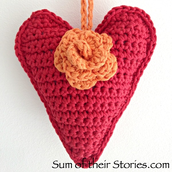A red crocheted sachet shaped like a heart with an orange flower from Sum of their Stories.