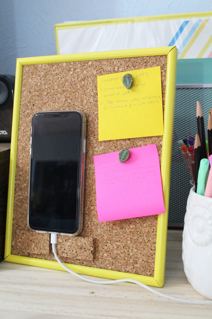 DIY phone stand made from framed cork board on a desktop