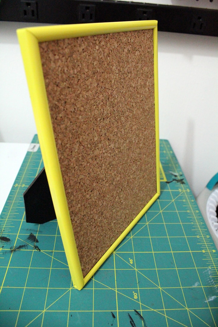 cork board in a yellow picture frame standing on a table