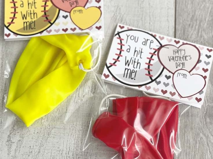 Baseball and softball valentine on a wood background; Note reads: You are a hit with me.
