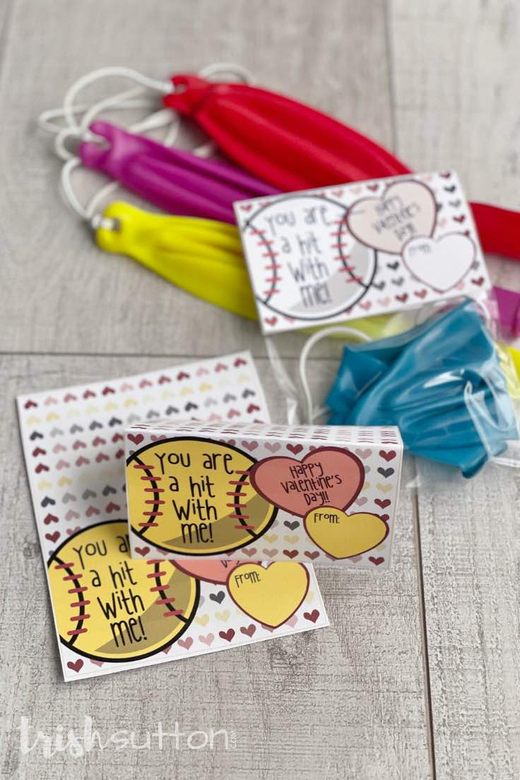 Kids valentine note cards with punch balloons on a wood background.