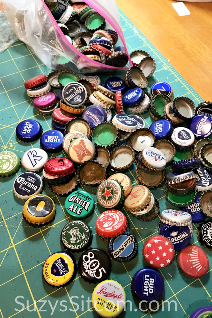 A pile of metal bottle caps for assorted drinks on a craft table.
