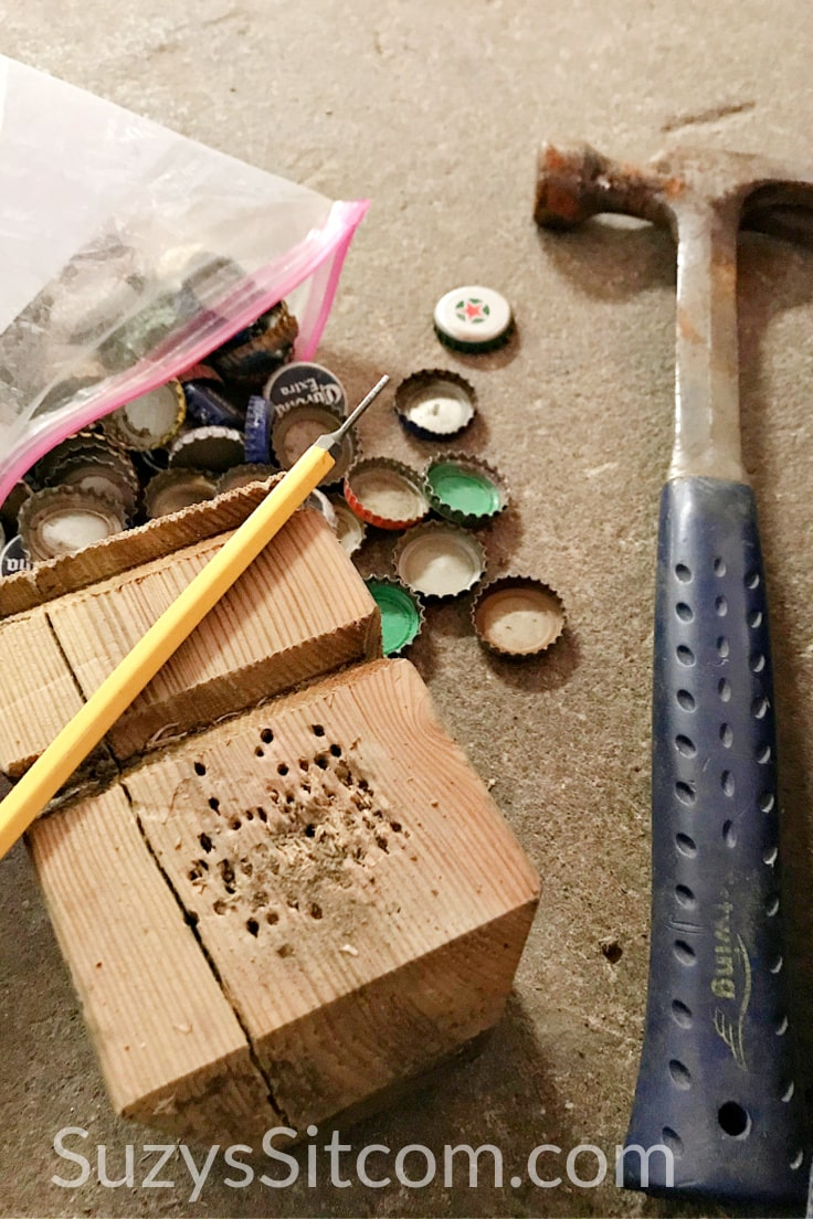 A hammer and bottle caps beside a wood block and awl.