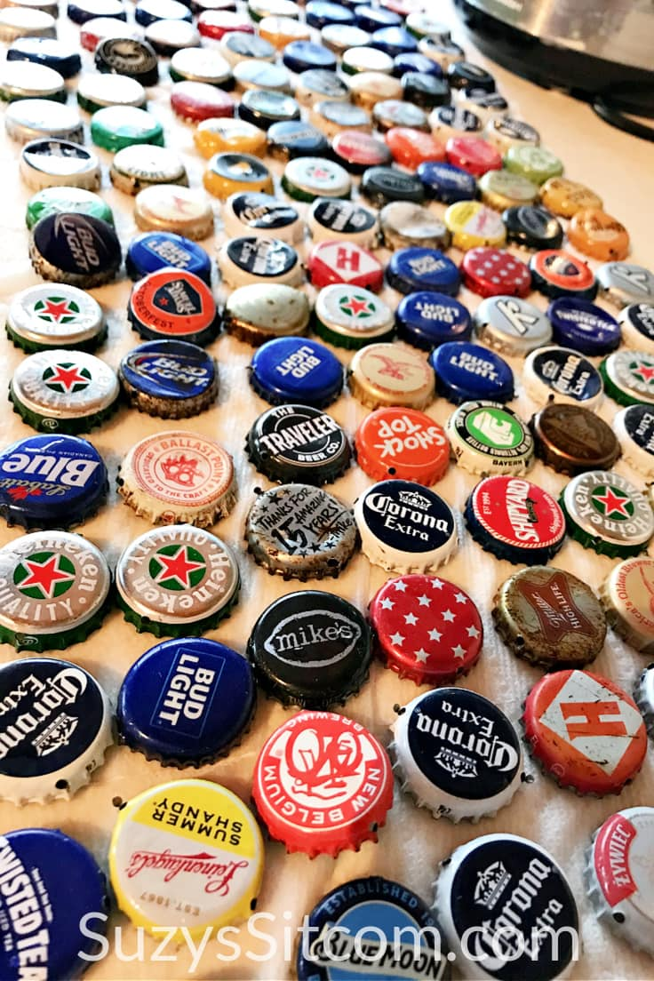A table full of bottle caps spread out with the tops facing up.