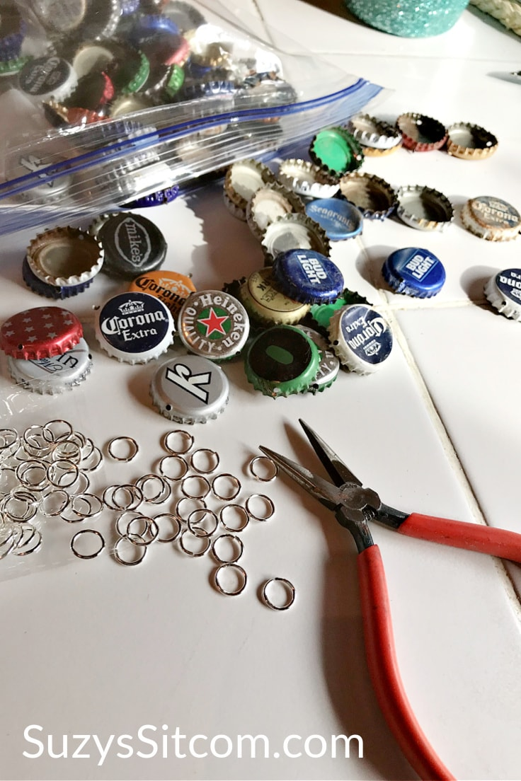 Needle nose pliers and bottle caps on a table beside a bag of metal jump rings.