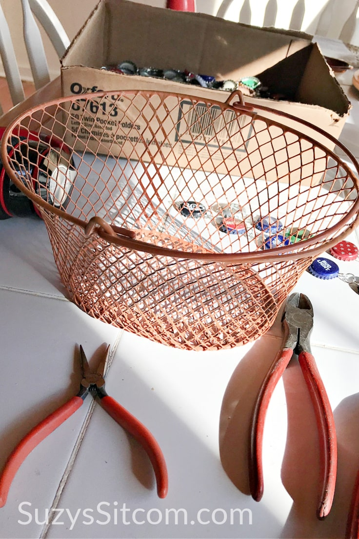 A wire basket on a table beside 2 pair of pliers.