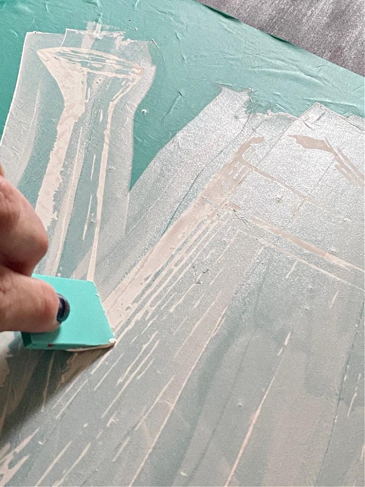 brushing white chalk paste onto the chalkboard sign