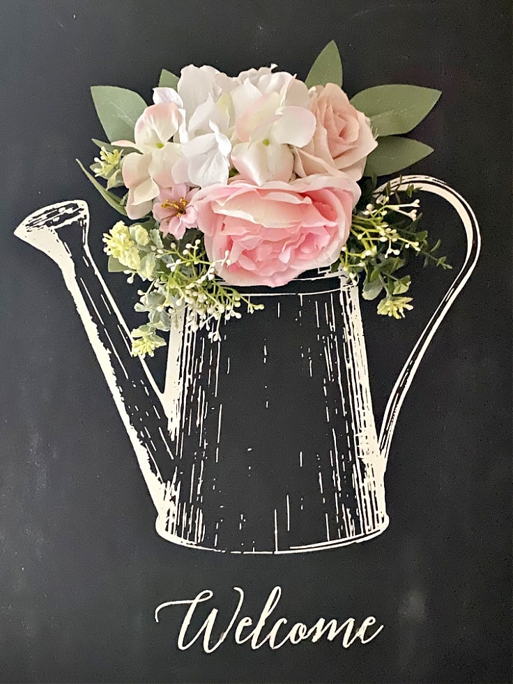 A chalkboard sign of a watering can that reads