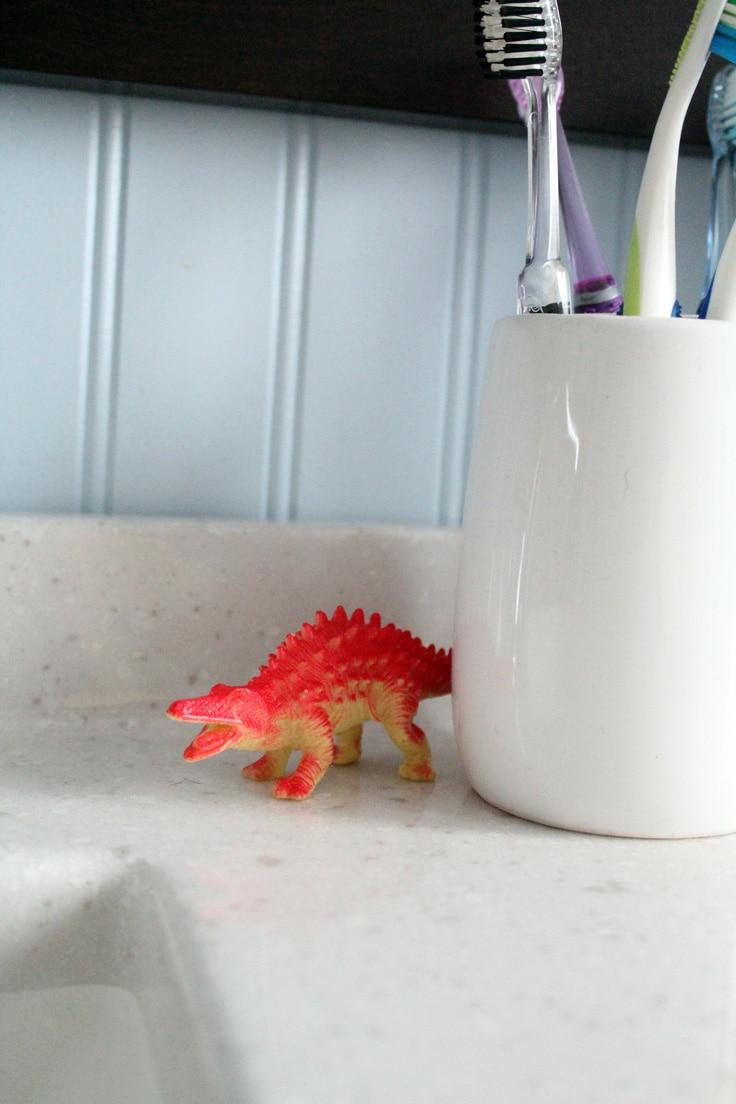 Orange plastic dinosaur on a bathroom sink beside a toothbrush holder.