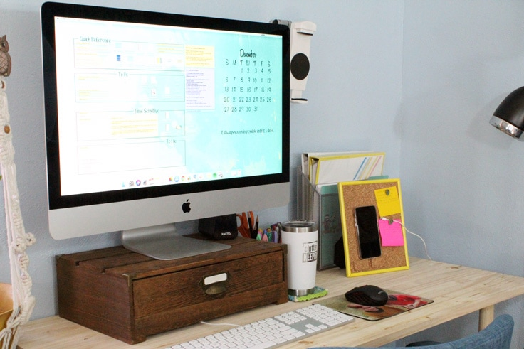 Organized desk with a cork board phone charger stand beside the monitor