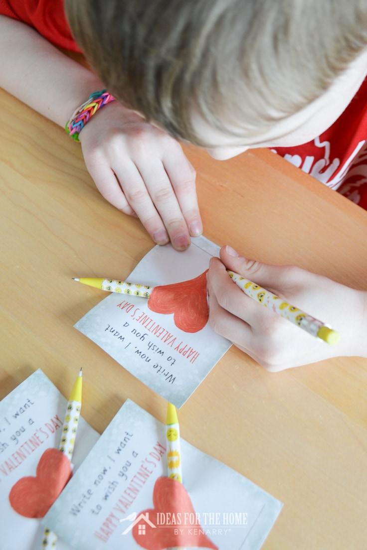 Child using a pencil to sign his Valentine's Day cards.