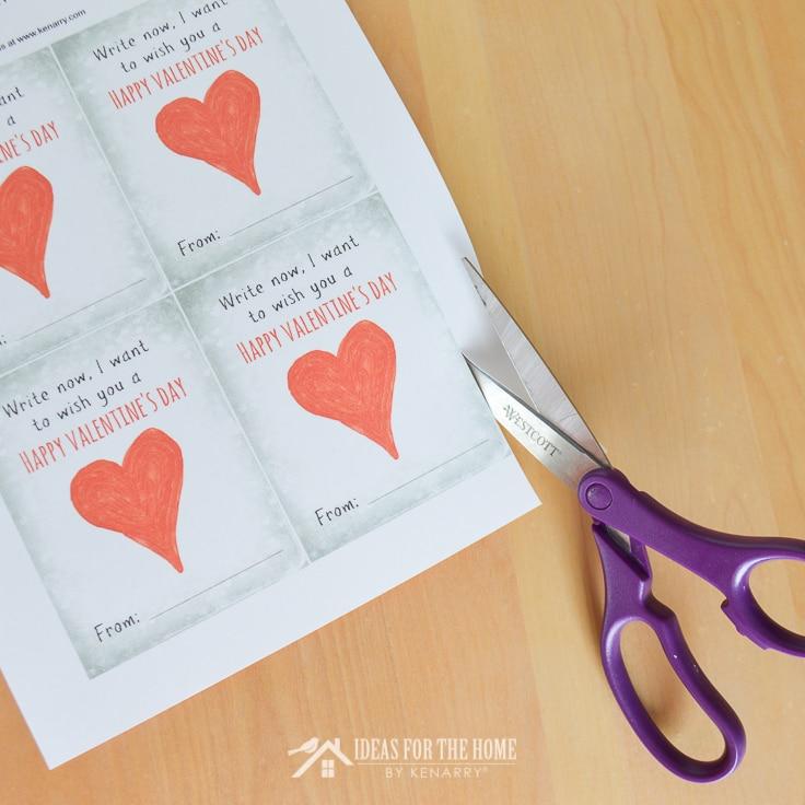 Scissors cutting apart kids' Valentine's Day cards.