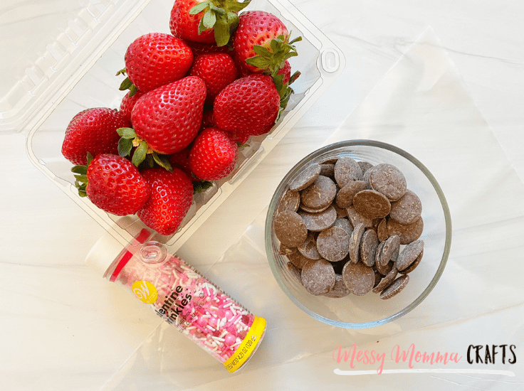 Sprinkles, strawberries, and a bowl of chocolate melts on a kitchen countertop.